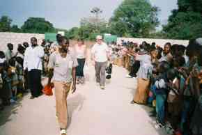 Pippa and Ian walk towards Bakalarr School between lines of clapping children
