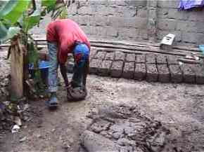 a man takes a quantity of mud and shapes it on the ground with a rolling action