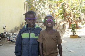 Some children at a compound wearing pipecleaner glasses made by Abdoulie