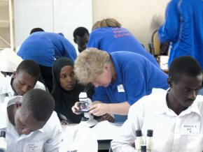 Cathy shows a student how to use a microscope