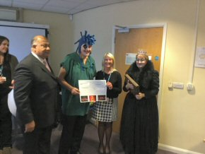 Carol receiving the 'cheque' from Jagtar Singh