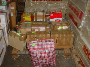 cardboard boxes and other packages stacked ready to be loaded into a container in the UK
