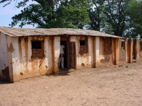the kitchen is a rust streaked single storey building with a very uneven corrugated iron roof