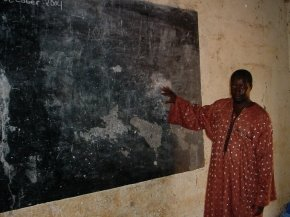a teacher shows the blackboard which has large patches of its black surface missing