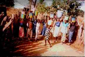 children and villagers bring water in buckets on their heads