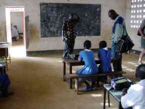 Kemo watches a class in progress in one of the classrooms with a new concrete floor