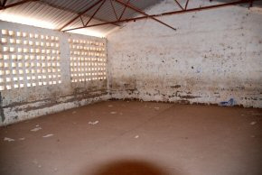 One of the classrooms with no furniture and cracked floor and damaged walls