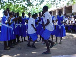 children at Jarreng in blue uniforms - the boys dance while the girls look on and clap