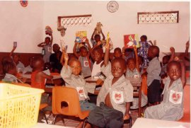 children at KMJ nursery school seated and grinning at the camera