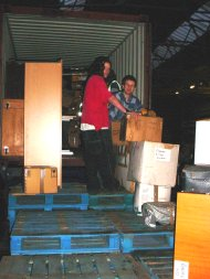 furniture and other pakages being loaded into the container