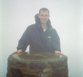 Chris posing by the trignometry point at the top of Snowdon