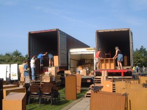 9am - two container trucks and a smaller van being loaded with furniture in the open air
