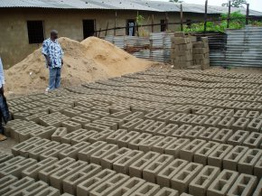 concrete blocks made on site drying out in rows with a large pile of sand behind