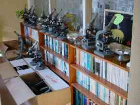 A row of optical microscopes stands on a bookcase awaiting packing