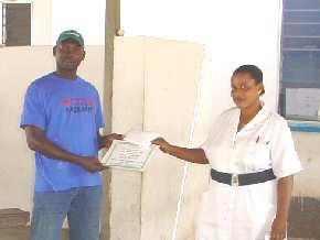 Clinic Administrator receiving certificate describing the gift from Kemo