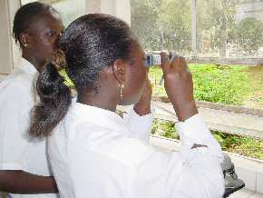 a student using  the Trekker microscope to look at a prepared slide