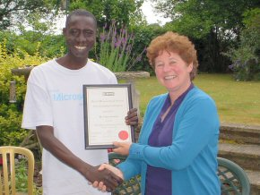 Omar is presented with his Bursary Certificate by RMS Fellow Kathy Groves