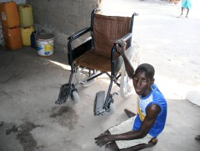 Sarjo at home - his old wheelchair does not work well on the sandy roads to school