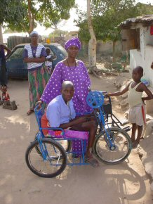 Sarjo and his new wheelchair at home with his Mum