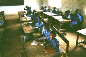 children sitting at their desks in a classroom at Bakalarr showing the old sand floor