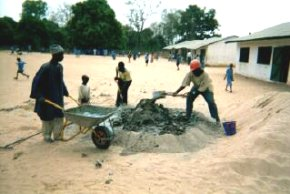 parents and staff mixing concrete in the school grounds