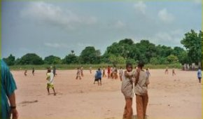 the school grounds with children playing on a large sandy area
