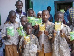 a group of school students hold up packets of seeds donated by Unwins and Suttons