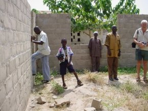 Ian and members of the staff look at the partly built walls of the classroom block