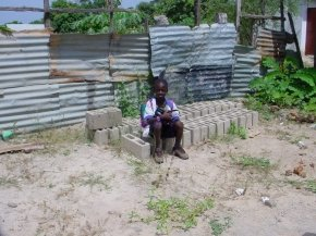 EB, one of the pupils at the school, sits on a pile of concrete blocks
