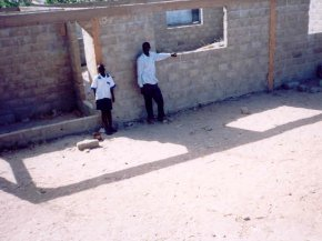 Science Club Coordinator, Omar Janneh, and a pupil stand in front of the building, with the walls completed to roof level