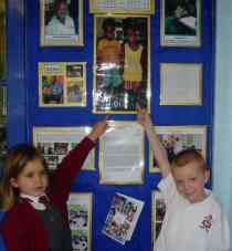 two children point to a picture of Abdoulrahman and Yusupha on the school notice board