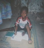 a boy squats in the ground with his sponsorship form