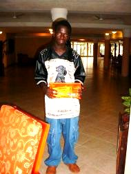 Alieu can now progress to Further Education, and poses with his sponsorship documents