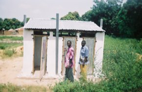 the toilet block has been completed, painted white and finished with doors and a corrugated iron roof