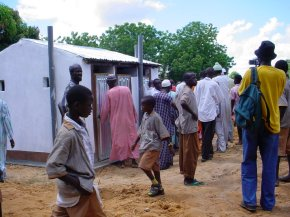 a toilet block is surrounded by a group of adults and children some of whom look inside