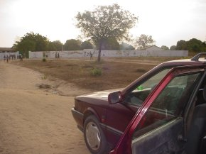 view of Bakalarr school from the approach road showing the boundary wall surrounding the school grounds