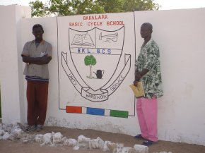 the two artists, Ousman and the art teacher, stand on either side of the painting on this panel which is the school badge