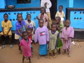 some children from Wandifa's extended family pose in front of a bright blue house